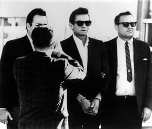 1965, Ελ Πάσο. Ο τραγουδιστής Τζόνι Κας οδηγείται στο δικαστήριο στο Τέξας. Συνελήφθη στο αεροδρόμιο με 1,000 ναρκωτικά χάπια στην κατοχή του.