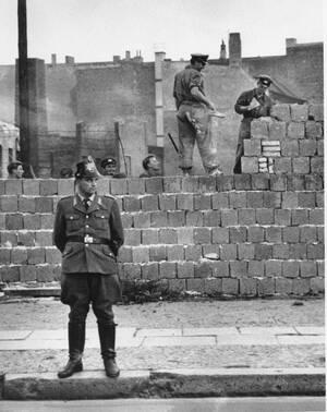 1961, Βερολίνο. Ένας Δυτικογερμανός αστυνομικός στέκεται μπροστά από τον τοίχο που χωρίζει το Δυτικό από το Ανατολικό Βερολίνο, στην οδό Μπερνάουερ, καθώς πίσω του Ανατολοκογερμανοί εργάτες προσθέτουν τούβλα στον τοίχο για να τον ανυψώσουν.