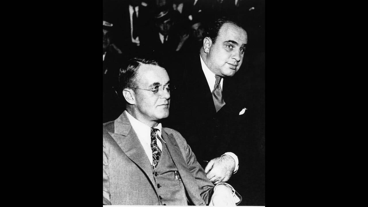 1931, Σικάγο. Ο Αλ Καπόνε (όρθιος, πίσω) ακούει τις εναντίον του κατηγορίες για φοροδιαφυγή στο ομοσπονδιακό δικαστήριο του Σικάγο. Δίπλα του κάθεται ο δικηγόρος του, Μάικλ Άχερν.