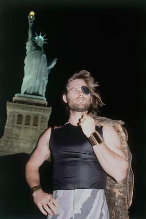 """1980, Νέα Υόρκη. Ο Κερτ Ράσελ, που ερμηνεύει το ρόλο του Σνέικ Πίλσεν, στην ταινία """"Απόδραση από τη Νέα Υόρκη"""", ποζάρει μπροστά στο άγαλμα της Ελευθερίας, κατά τη διάρκεια των γυρισμάτων."""
