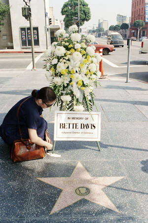 """1989, Χόλιγουντ. Μια θαυμάστρια τοποθετεί λουλούδια στο άστρο της Μπέτι Ντέιβις, στο """"Walk of Fame"""", του Χόλιγουντ. Η ηθοποιός πέθανε από καρκίνο, στο Παρίσι, σε ηλικία 81 ετών."""