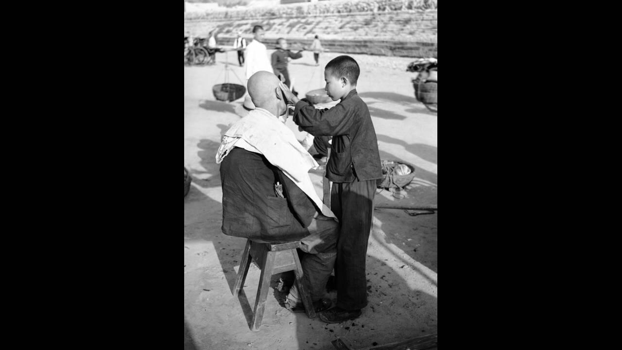 1936, Πεκίνο. Στην Κίνα, αγόρια από 10-16 ετών κάνουν τους κουρείς στο δρόμο. Οι πελάτες κάθονται όπου βρουν, το κούρεμα κοστίζει μια πένα και το ξύρισμα μισή.