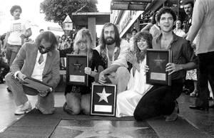 """1979, Χόλιγουντ. Τα μέλη του συγκροτήματος Fleetwood Mac ποζάρουν μπροστά στο """"αστέρι"""" τους στο Walk of Fame. Από αριστερά, Τζον ΜακΒι, Κριστίν ΜακΒι, Μικ Φλίτγουντ, Στίβι Νιξ και Λίντσεϊ Μπάκινχαμ."""