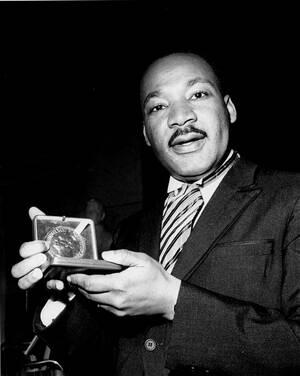 1964, Όσλο. Ο Δρ. Μάρτιν Λούθερ Κινγκ δείχνει το βραβείο Νόμπελ Ειρήνης που του επενεμείθη. Ο 35χρονος Κινγκ τιμήθηκε για την προώθηση της μη-βίας στο κίνημα των κοινωνικών δικαιωμάτων.