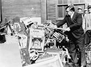 """1934, Νέα Υόρκη. Ο Δήμαρχος της Νέας Υόρκης, Φιορέλο Λα Γκουάρντια καταστρέφει μηχανήματα τζόγου, τους γνωστούς """"κουλοχέρηδες"""", στη μάχη τους κατά του τζόγου στην πόλη. τα μηχανήματα πετάχτηκαν τελικά στον ποταμό Χάντσον."""
