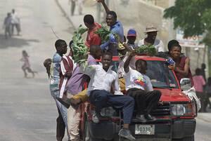 1994, Αϊτή. Κάτοικοι της Αϊτής πανηγυρίζουν στους δρόμους του Πορτ Ο Πρενς, για την επιστροφή του Προέδρου Ζαν Μπερτράντ Αριστίντ. Η επιστροφή του πρώην ιερέα που έγινε πολιτικός, έδωσε νέες ελπίδες στους Αϊτινούς, ότι η Δημοκρατία μπορεί επιτέλους να επι