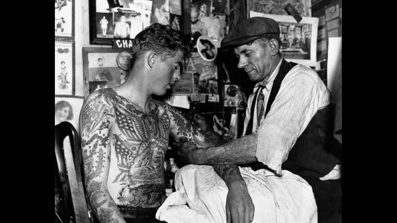 """1935, Νέα Υόρκη. Τα τατουάζ δεν είναι νέα μόδα, όχι για όλους τουλάχιστον. Ο Τσαρλς Βάγκνερ (δεξιά) """"χτυπάει"""" τατουάζ στους πελάτες του εδώ και 45 χρόνια."""