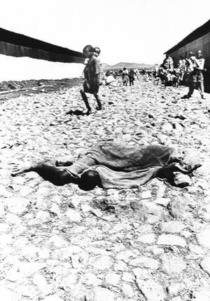 1984, Αιθιοπία. Το νεκρό σώμα ενός θύματος της πείνας που θερίζει στην Αιθιοπία, κείται στη μισοσκεπασμένο σε ένα πλακόστρωτο στην πόλη Κορέμ, στα βόρεια της χώρας. Υπολογίζεται ότι 100.000 άνθρωποι που υποφέρουν από το λιμό, έχουν συγκεντρωθεί εδώ αναζητ