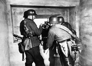 1938, Ρήνος. Τρεις Γερμανοί στρατιώτες επανδρώνουν ένα οπλοπολυβόλο στις όχθες του Ρήνου, στη γραμμή Ζίγκφριντ, απέναντι από τη Γαλλία και την αντίστοιχη αμυντική γραμμή Μαζινό.
