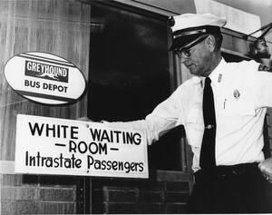 """1961, Μιλγουόκι. Ένας αστυνομικός ποζάρει μπροστά στην ταμπέλα που γράφει """"αίθουσα αναμονής για λευκούς"""", στο σταθμό των λεωφορείων. Η ταμπέλα αναρτήθηκε μια μέρα μετά την ανακοίνωση ότι ο διαχωρισμός λευκών και μαύρων στους σταθμούς των λεωφορείων πρόκει"""