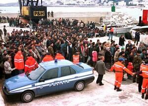 """1997, νότια Ιταλία. Στο λιμάνι της Santa Maria di Leuca η ιταλική αστυνομία ελέγχει την άφιξη περίπου 800 προσφύγων, κυρίως Κούρδων, που αποβιβάστηκαν από το πλοίο """"Hussam"""". Ανάμεσα στους επιβάτες είναι και Τούρκοι κουρδικής καταγωγής, Πακιστανοί και Αιγύ"""