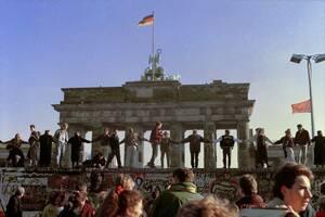 1989, Βερολίνο. Βερολινέζοι χορεύουν και τραγουδούν πάνω στο τείχος του Βερολίνου για να γιορτάσουν το άνοιγμα των συνόρων ανάμεσα στη Δυτική και την Ανατολική Γερμανία.