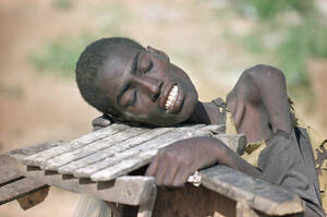 1992, Σομαλία. Ένας αποστεωμένος από την πείνα Σομαλός κρατιέται από ένα κάρο έξω από ένα κέντρο βοήθειας, στη Μπαϊντόα, 200 χιλιόμετρα από το Μογκαντίσου. Τριανταπέντε φορτηγά με τρόφιμα  που στέλνουν οι διεθνείς οργανισμοί στην περιοχή κατασχέθηκαν από