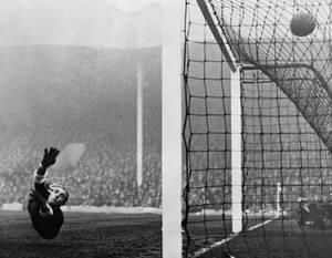 1934, Λονδίνο. Ο Ιταλός τερματοφύλακας Κάρλο Καρεσόλι προσπαθεί ανεπιτυχώς να σταματήσει τη μπάλα κατά τη διάρκεια ενός αγώνα ανάμεσα στην Αγγλία και την Ιταλία, στο στάδιο Χάιμπουρι της Άρσεναλ.