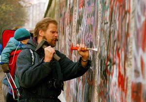 1989, Βερολίνο. Ένας Δυτικογερμανός με το μωρό του στην πλάτη, κόβει ένα κομμάτι από το τείχος του Βερολίνου. Άνθρωποι απ' όλα τα μέρη του κόσμου έρχονται στο Βερολίνο για να πάρουν ένα κομμάτι του τοίχου μετά την πτώση του.
