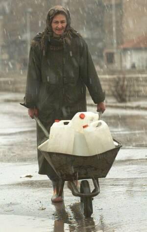1995, Σαράγιεβο. Μια γυναίκα σπρώχνει ένα καρότσι, μεταφέροντας πόσιμο νερό στο κέντρο του Σαράγιεβο. Παρότι η παροχή νερού έχει αποκατασταθεί στην πόλη, δεν είναι διαρκής και απρόσκοπτη, κι έτσι οι κάτοικοι αναγκάζονται να κρατάνε αποθέματα στα σπίτια το