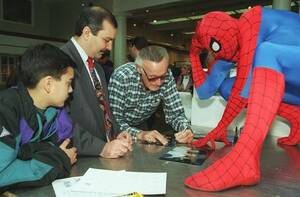 1995, Νέα Υόρκη. Ο Σπάιντερμαν κοιτάει τον δημιουργό του, Σταν Λι, ο οποίος υπογράφει αυτόγραφα, στον οίκο δημοπρασιών Christie's στη Νέα Υόρκη. Από το Σπάιντερμαν ως τον Απίθανο Χαλκ, αντικείμενα των παλιών χαρακτήρων της Μάρβελ βγαίνουν σε δημοπρασία απ