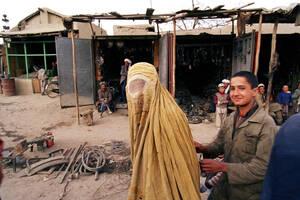 """1991, Καμπούλ. Μια Αφγανή με το παιδί της περπατούν μπροστά από άδεια καταστήματα στην αγορά που είναι γνωστή ως το """"Παζάρι του Μπρέζνιεφ"""" στην Καμπούλ. Η περιοχή ήταν κάποτε ένα πολυσύχναστο εμπορικό σημείο, με βασικούς πελάτες τους Σοβιετικούς στρατιώτε"""