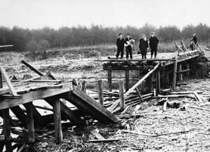 """1956, Ουγγαρία. Ούγγροι πρόσφυγες στέκονται μπροστά στη """"γέφυρα της ελευθερίας"""", η οποία ανατινάχθηκε από τα ρωσικά στρατεύματα. Η γέφυρα, μια ξύλινη κατασκευή στα σύνορα με την Αυστρία, ήταν ένα από τα περάσματα για τους Ούγγρους που ήθελαν να διαφύγουν"""