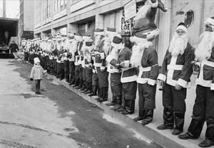 """1962, Νέα Υόρκη. Ένας πιτσιρικάς """"επιθεωρεί"""" μια μικρή στρατιά από Άγιους Βασίληδες, στην 8η Λεωφόρο της Νέας Υόρκης. Οι συγκεκριμένοι Άγιοι θα προσπαθήσουν να μαζέψουν χρήματα από τους περαστικούς για φιλανθρωπικούς σκοπούς στη διάρκεια των εορτών."""
