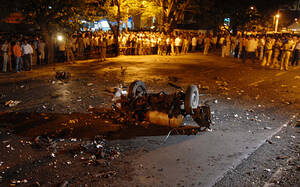 2008, Βομβάη. Ένα κατεστραμμένο όχημα στο δρόμο, στο σημείο όπου σημειώθηκε μια από τις εκρήξεις που συγκλόνισαν τη Βομβάη. Ένοπλοι εισέβαλαν σε πολυτελή ξενοδοχεία και σε έναν σιδηροδρομικό σταθμό, σε επτά ταυτόχρονες επιθέσεις στο οικονομικό κέντρο της