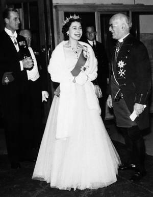 1957, Λονδίνο. Η βασίλισσα Ελισάβετ και ο πρίγκιπας Φίλιππος, με τον Αρχιεπίσκοπο του Κάντερμπέρι, έναν εκ των διαχειριστών του Βρετανικού Μουσείου, σε δεξίωση που παραθέτει το Μουσείο προς τιμήν τους. Η βασίλισσα φοράει μακριά τουαλέτα από λευκό τούλι, δ
