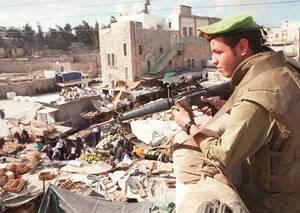 1996, Χεβρόνα. Ένας Ισραηλινός στρατιώτης παρακολουθεί την αραβική αγορά από τη θέση του σε οροφή κτηρίου του Εβραϊκού τομέα της Χεβρόνας. Οι διαπραγματεύσεις Ισραηλινών και Παλαιστινίων έχουν παρουσιάσει κάποια πρόοδο και η ισραηλινή πλευρά δηλώνει έτοιμ