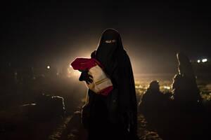 25 Φεβρουαρίου, Συρία. Μια γυναίκα και το μωρό της, που έχουν απομακρυνθεί από την τελευταία περιοχή η οποία βρισκόταν υπό την κατοχή του Ισλαμικού Κράτους, περπατούν στην έρημο έξω από το Μπαγκούζ της Συρίας, αφού προηγουμένως έχουν περάσει από τον έλεγχ
