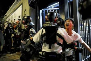 31 Ιουλίου, Χονγκ Κονγκ. Ένας αιμόφυρτος άντρας απομακρύνεται από την αστυνομία από το σημείο στο οποίο δέχτηκε επίθεση από διαδηλωτές, έξω από το αστυνομικό τμήμα του Κουάι Τσουνγκ, στο Χονγκ Κονγκ.