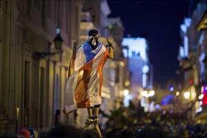 17 Ιουλίου. Διαδηλωτής που φοράει στη σημαία του Πουέρτο Ρίκο, συμμετέχει σε πορεία μαζί με χιλιάδες ακόμα προς την οικία του κυβερνήτη, Ρικάρντο Ροσέλο, στο Σαν Χουάν. Οι διαδηλωτές ζητάνε την παραίτηση του κυβερνήτη, μετά τη διαρροή συνομιλιών του στις