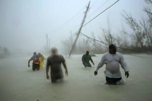 13 Σεπτεμβρίου 2019. Εθελοντές περπατούν σε έναν πλημμυρισμένο δρόμο, ενάντια στον άνεμο και τη βροχή, για να σώσουν οικογένειες που παγιδεύτηκαν από τον τυφώνα Ντόριαν σε γέφυρα στο Φρίπορτ, στις Μπαχάμες.