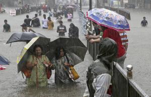 4 Σεπτεμβρίου, Μουμπάι. Άνθρωποι προσπαθούν να διασχίσουν έναν πλημμυρισμένο δρόμο στο Μπουμπάι της Ινδίας, που πλήττεται από τους μουσώνες.