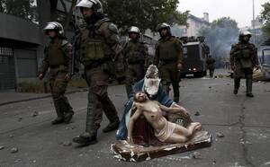 8 Νοεμβρίου, Χιλή. Η αστυνομία κυνηγάει διαδηλωτές, περνώντας δίπλα από ένα άγαλμα το οποίο οι διαδηλωτές πήραν από μια εκκλησία.