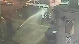 Αστυνομικοί βρέχουν με μάνικα γυναίκα που περνά έξω από Τμήμα