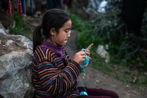 Ένα κορίτσι πλέκει καθισμένο σε μία πέτρα. Γύρω της δεκάδες εστίες μικροβίων από σκουπίδια αποτελούν κίνδυνο για μικρούς και μεγάλους.