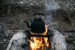 Ένας βραστήρας νερού, κατάμαυρος από την φωτιά, πάνω σε μία αυτοσχέδια εστία.