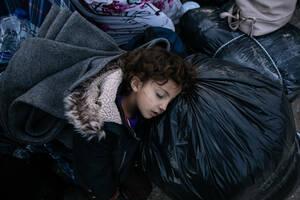 Ένα κορίτσι κοιμάται πάνω σε σακούλες με πράγματα, περιμένοντας το λεωφορείο. Είναι άλλοι 200 «τυχεροί» που θα αφήσουν πίσω τους τη Μόρια.