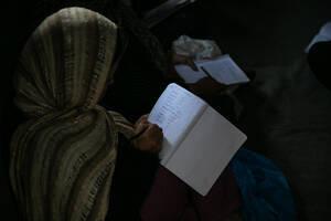 Μία γυναίκα γράφει στο τετράδιό της κατά τη διάρκεια μαθήματος αγγλικών σε μία αυτοσχέδια αίθουσα διδασκαλίας.