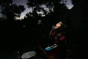 Ένα κορίτσι από το Αφγανιστάν τρώει βραδινό, υπό το φως ενός φακού