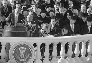 1961, Ουάσινγκτον. Ο Τζον Φιτστζέραλντ Κένεντι απευθύνεται στον αμερικανικό λαό, λίγη ώρα μετά την ορκομωσία του. Πίσω του διακρίνονται ο αντιπρόεδρος Λίντον Τζόνσον, ο Ρίτσαρντ Νίξον και ο πρώην Πρόεδρος Χάρι Τρούμαν.