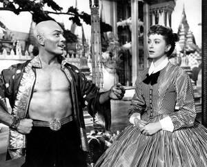 """1957 Ο Γιουλ Μπρίνερ και η Ντέμπορα Κερ στο σετ της ταινίας """"Ο βασιλιάς κι εγώ"""". Ο Μπρίνερ, στο ρόλο του βασιλιά Μονγκούτ και η Λερ, στο ρόλο της Άννα, πρωταγωνιστούν στην κινηματογραφική εκδοχή του ομώνυμου μιούζικαλ του 1951."""