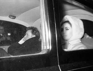 1963, Λονδίνο. Η Ελίζαμπεθ Τέιλορ και ο Ριτσαρντ Μπάρτον στο Λονδίνο, φανερά ενοχλημένοι από το κυνηγητο κοινού και παπαράτσι.