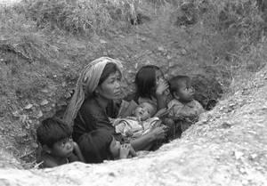 1975, Καμπότζη. Μια γυναίκα με τα παιδια τς περιμένουν να σταματήσει η ανταλλαγή πυρών για να βγουν από το χαντάκι στο οποίο έχουν βρει καταφύγιο στην Πνομ Πενχ.