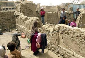 2002 Γείτονες τα λένε πάνω από έναν βομβαρδισμένο φράχτη που κάποτε χώριζε τα σπίτια τους στην Καμπούλ του Αφγανιστάν. Η επιστροφή πολλών προσφύγων στην κατεστραμένη πόλη, έχει δημιουργήσει μια άνευ προηγουμένου κρίση στέγασης.