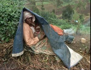 1997 Μια γυναίκα ταΐζει το μωρό της κάτω από ένα αυτοσχέδιο κατάλυμα, στο στρατόπεδο προσφύγων της Καρούμπα, βόρεια από τη Γκόμα. Εκατοντάδες πρόσφυγες από τη Ρουάντα προσπαθούν να επιβιώσουν στην ορεινή αυτή περιοχή, περιμένοντας κάποια βοήθεια.