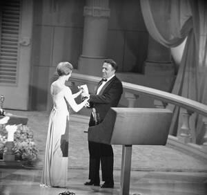 """1964, Λος Άντζελες. Ο σκηνοθέτης Φεντερίκο Φελίνι δέχεται το Όσκαρ καλύτερης ξενόγλωσσης ταινίας από την ηθοποιό Τζούλι Άντριους για την ταινία του """"8½""""."""