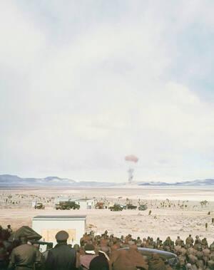 1955, Νεβάδα.  Στο βάθος, η έκρηξη από μια ατομική βόμβα 22 κιλοτόνων, στο πεδίο πυρηνικών δοκιμών, στην έρημο της Νεβάδα.