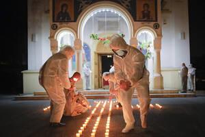 Ειδικές ομάδες ανάβουν κεράκια σε σχήμα σταυρού έξω από ορθόδοξη εκκλησία στην Ρουμανία