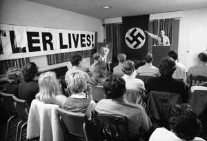 1978, Άρλινγκτον, Βιρτζίνια. Ο Ματ Κολ χαιρετάει τους συγκεντρωμένους, ανοίγοντας μια μυστική τελετή του Εθνικοσοσιαλιστικού Κόμματος στο Άρλινγκτον. Η τελετή γίνεται για τους εορτασμούς της 89ης επετείου από τη γέννηση του Αδόλφου Χίτλερ.