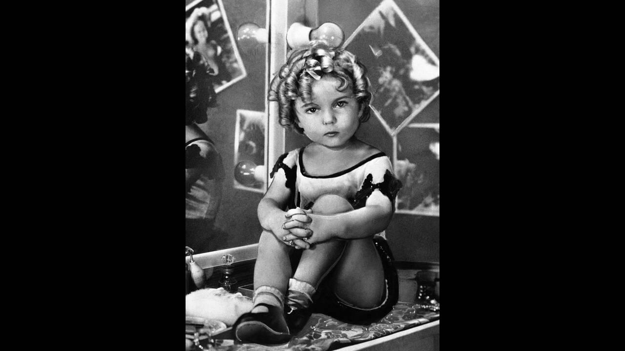 1932, άγνωστη τοποθεσία.  Η ηθοποιός Σίρλεϊ Τεμπλ, ποζάρει με τον αέρα μιας σταρ. Είναι μόλις 4 ετών, καθώς γεννήθηκε στις 23 Απριλίου του 1928.
